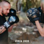Couple boxing with womens black and gold skull focus pads