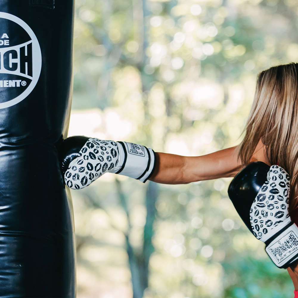 Women punching boxing bag with Womens Black Lip Art Boxing Gloves
